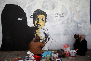 A friend of artist Haifa Subay takes pictures for her while she paints a mural about children and women suffering in the time of war in Sanaa