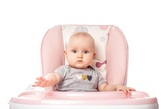happy baby sitting in a high chair isolated on white background. place for text