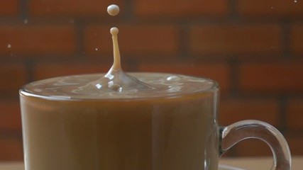 Fototapete - Drop fresh milk into a glass full of milk coffee in Slow Motion
