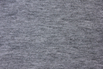 Knitted dark gray natural fabric texture background. Grey cloth pattern of hoodie, sweater, pullover or shirt. Casual lifestyle clothing material design, close up top view with empty copy space