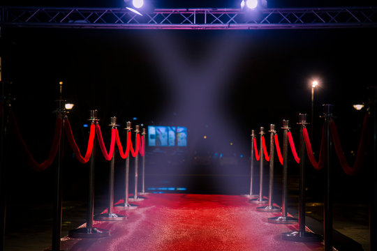 Red carpet with  barriers, velvet ropes and lights in the background