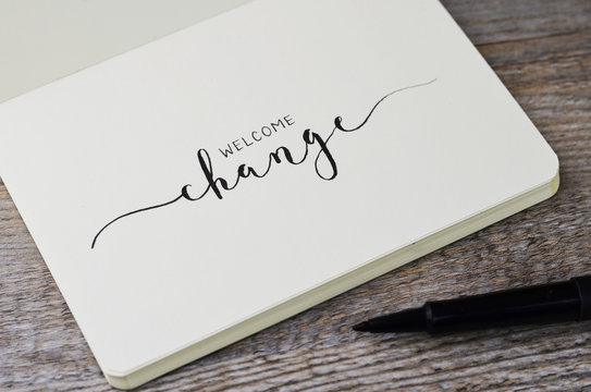 WELCOME CHANGE hand lettering in notebook with pen on wooden background