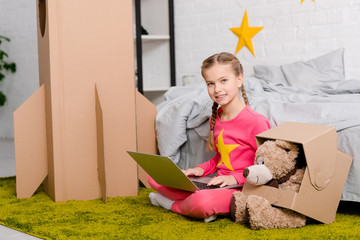 Smiling kid with teddy bear sitting on carpet and using laptop in bedroom