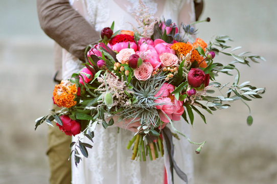 Bride holding a gorgeous bohemian wedding bouquet with peonies, roses and poppy flowers