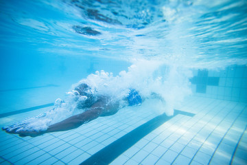 Underwater image of a male swimmer diving into an olympic swimming pool to train