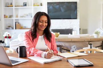 Smiling mixed race retired woman sitting at a table writing in her dining room, waist up