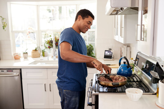 Young adult black man standing in the kitchen cooking on the hob, using a spatula and frying pan, side view, close up