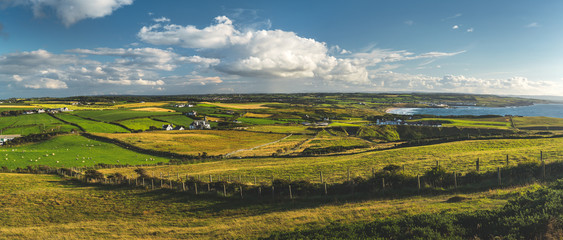 Photo sur Plexiglas Bleu jean Countryside panoramic view of the green fields under the blue cloudy sky. Northern Ireland landscape. Stunning pastures of the English village. Picturesque grass covered land next to the shoreline.