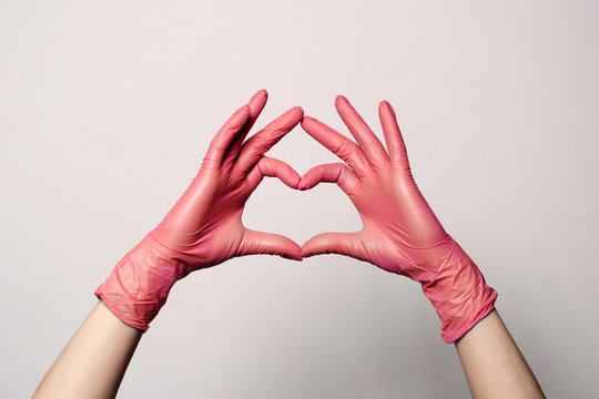 Closeup of a hand in latex rubber medical pink gloves folded into a heart sign. Isolated on white background. Concept love couple couple valentine