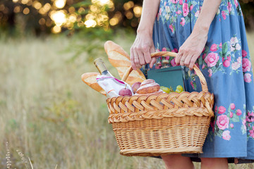 Canvas Prints Picnic Summer - picnic in the meadow. girl holding a basket for a picnic with baguette, wine, glasses, grapes and rolls