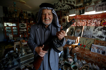 Youssef Akkar, 80, an Iraqi retired teacher poses for a picture in his museum at home in Najaf