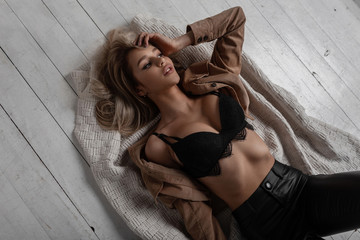 Sexy glamorous young woman with a beautiful body in a shirt in a black stylish bra in fashionable leather black pants lies on a vintage wooden white floor in the studio. Luxurious girl.View from above