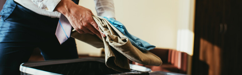 cropped view of businessman putting clothes into travel bag