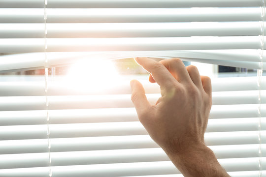 Young man opening window blinds, closeup. Space for text