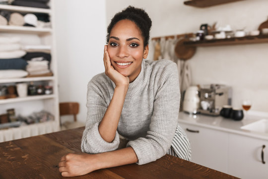 Young attractive smiling african american woman with dark curly hair leaning on table happily looking in camera while spending time in beautiful cozy kitchen at home