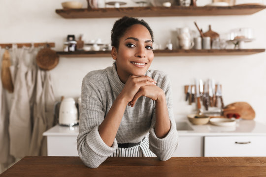 Young pretty smiling african american woman with dark curly hair leaning on table happily looking aside while spending time in beautiful cozy kitchen at home