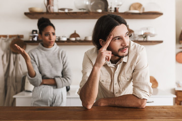 Angry man with beard leaning on table while sadly looking aside with emotional african american woman on background. Young international couple in quarrel spending time in kitchen at home