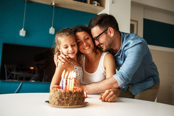 Mother's birthday.Husband and daughter surprise they mother and wife with birthday cake .