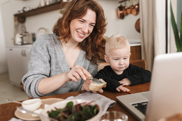 Young cheerful woman with red hair in knitted sweater and little son sitting at the table with food and happily watching cartoons on laptop. Mom spending time with her baby in kitchen at home