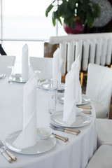 closeup white napkins stand in  white plates on served table in the restaurant. clean white dishes layout on a white tablecloth