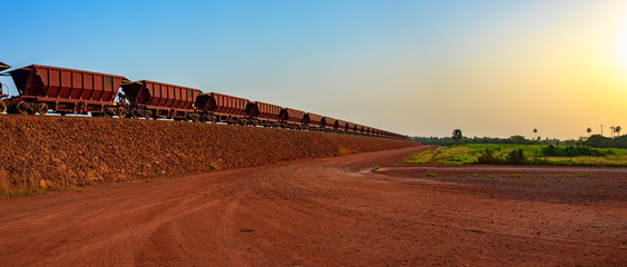 Photo sur Toile Afrique Railway carriages for transportation of bauxite ore on train tracks at the end of the railway line from bauxite mining. Guinea, Africa.