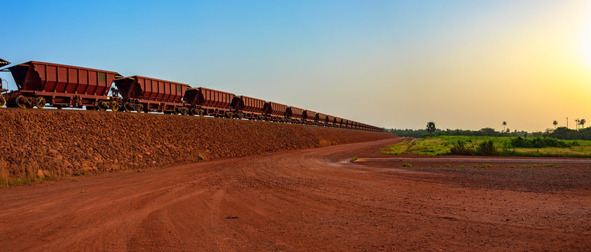 Railway carriages for transportation of bauxite ore on train tracks at the end of the railway line from bauxite mining. Guinea, Africa.