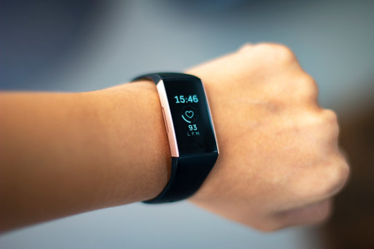 Woman monitoring her heart beat with an activity tracker wearable device on her wrist also known as fitness tracker