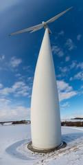 Panoramique grand angle d'une éolienne ressemblant à un Baobab, vue en contre plongée sur fond de ciel bleu en hiver