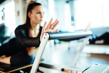 Two young females doing reformer exercises on pilates machines Fototapete