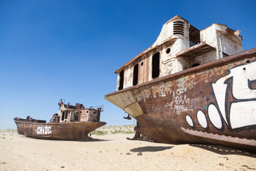 Rustic boats on a ship graveyards on a desert around Moynaq, Muynak or Moynoq - Aral sea or Aral lake - Uzbekistan in Central Asia