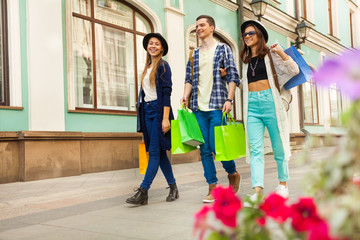 Guy and girls with shopping bags during travel
