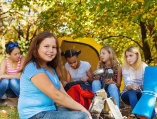 Cute large beautiful girl sitting near yellow tent