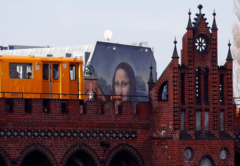 """A U-Bahn underground train passes by a mural by Berlin-based street art gang """"Die Dixons"""" (The Dixons) which features a giant reproduction of Leonardo da Vinci's artwork Mona Lisa"""