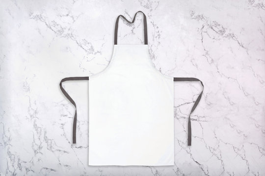 Mockup of white apron on marble background. Chef uniform template. Flat lay