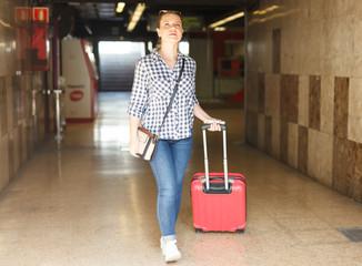 Girl with suitcase walking on underground station