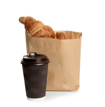 Paper bag with croissants and cup of coffee on white background. Space for design