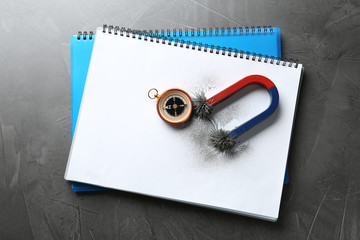 Notebooks, compass and magnet with iron powder on grey background, top view. Space for text