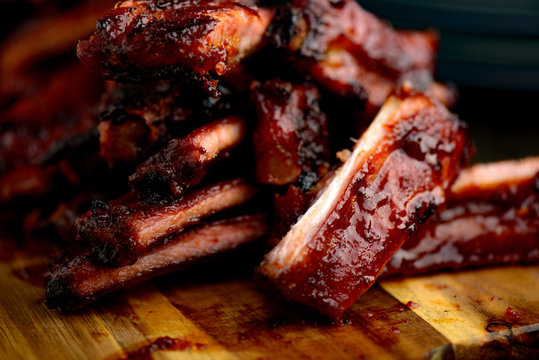 Smoked ribs ready to be eaten on wooden plate.