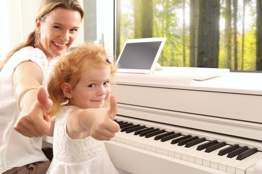 Mutter Klavierlehrerin Mädchen am Klavier
