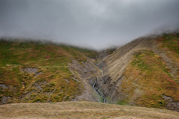 Mountain river flowing on green hill in the clouds