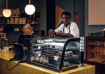 Two young multiracial baristas working at their trendy coffee shop.