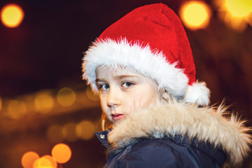 Cute little girl in red hat posing on the street with bokeh light, christmas time