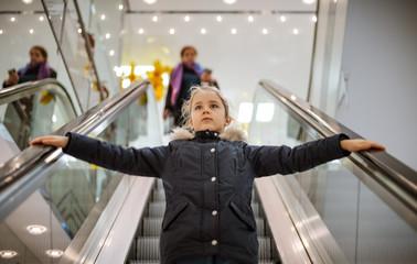 Little girl on the escalator in the shopping center