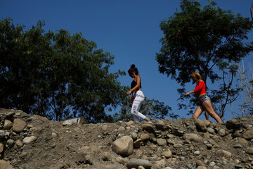 Women walk along a pathway near the Colombian-Venezuelan border in the outskirts of Cucuta