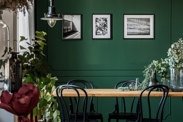 Green flowers in glass vase on long wooden table with black chairs in elegant living room Fototapete