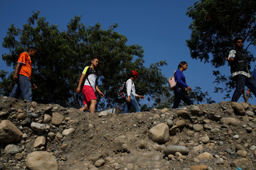 People walk along a pathway near the Colombian-Venezuelan border in the outskirts of Cucuta