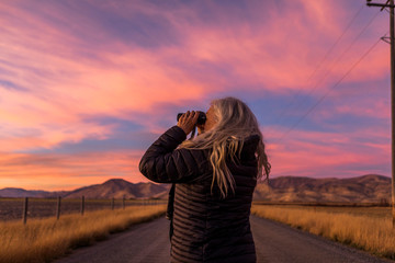 Woman using binoculars at sunset