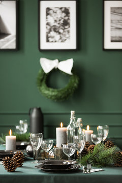 Vertical view of christmas garland and black and white posters on green wall of dining room set for christmas dinner