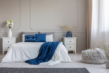 Copy space on empty grey wall of fashionable grey white and blue bedroom interior