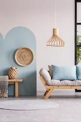 Wicker chandelier above wooden Scandinavian sofa with futon in bright living room interior
